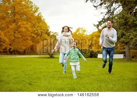 family, parenthood, leisure and people concept - happy mother, father and little girl running and playing catch game in autumn city park