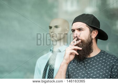 handsome bearded young man hipster with long beard and mustache has stylish hair in cap smoking cigarette near shop glass showcase with dummy in shirt and tie