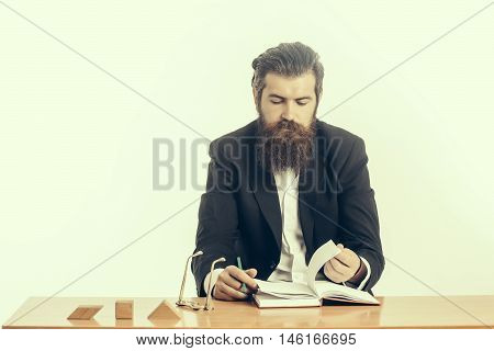young handsome bearded man scientist or professor with long beard and teacher glasses with book or notepaper sitting at table with wooden cubes isolated on white background