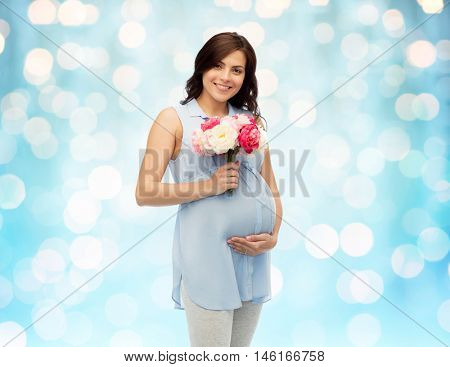 pregnancy, motherhood, holidays, people and expectation concept - happy pregnant woman with flowers touching her big belly over blue holidays lights background