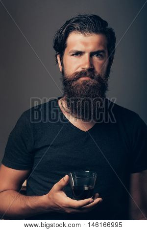 handsome bearded man with stylish hair mustache and beard on serious face in shirt drinking brandy or whiskey alcohol beverage from glass on grey background