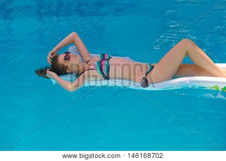 Young woman with attractive tanned sexy body in colorful bikini laying and relaxing on air mattress and floating on blue water of summer pool