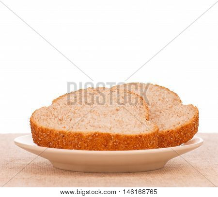 Fresh bread with bran on a plate over white background