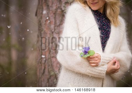 Young blond woman in white cardigan standing near an old tree and holding beautiful snowdrops in her hands. First spring flowers in a forest. Beginning of spring in a forest.