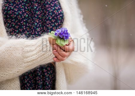 Beautiful snowdrops in hands of a young woman in white cardigan. First spring flowers in a forest. Beginning of spring in a forest.