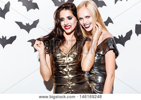 Portrait of two happy young women with scared halloween makeup standing and smiling over white background
