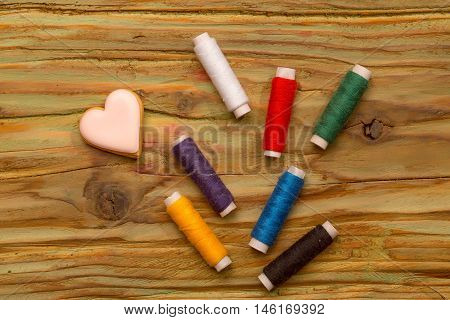 Many bobbins of bright colorful cotton threads for sewing homemade cookies in heart shape on wooden background