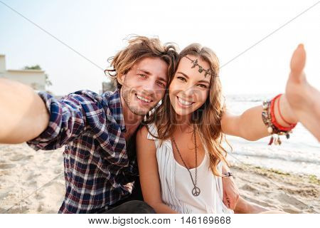 Happy young couple sitting and taking selfie on the beach