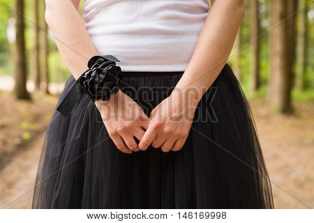 A young girl in a white tank top and black fluffy skirt in the forest outdoors. black flower wristband. Celebration party. Bridesmaid. Wedding.