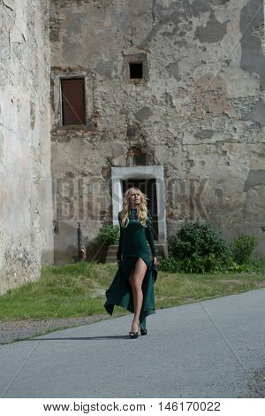 young pretty woman with long lush curly blonde hair and sexy bodies in green dresses walking near stony building with windows outdoor