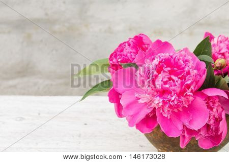 bouquet of pink peony in an old clay pot closeup on a light blurred background