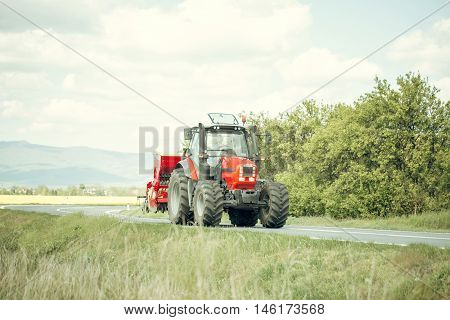 Red farm tractor drives on road along beautiful field on summer sunny day on landscape background