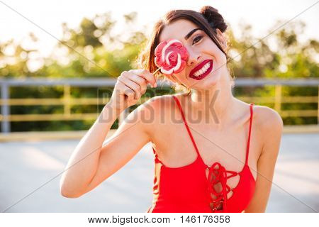 Cheerful playful young woman covered her eye with lollipop standing outdoors