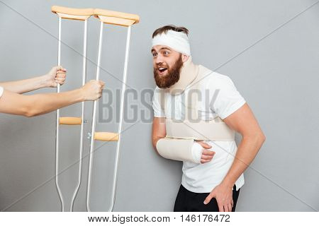 Satisfied happy bandaged bearded man taking crutches from female hands over gray background