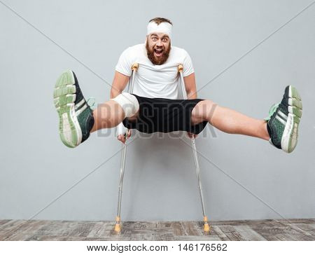 Freaky crazy young man playing with crutches and shouting over gray background