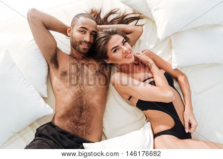 Image of happy multiracial couple laying at the white beach bed and looking at camera