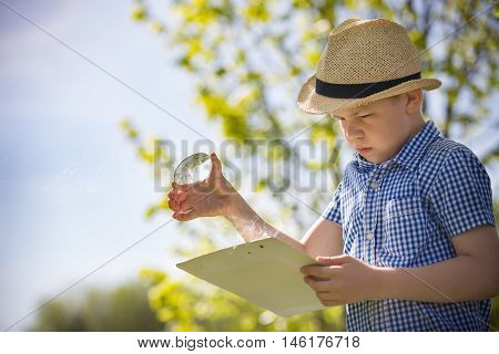 Adorable kid boy making fire on paper with a magnifying glass outdoors on sunny day. Child exploring fire nature in the garden. Young explorer with magnifier. Education and discovery concept