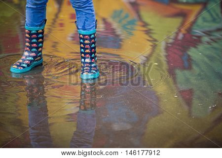 Kid boy in funny rubber boots standing in the puddle in the street after rain. Pair of colorful rubber boots in a big puddle with graffiti reflections. Boy having fun after rain. Outdoor.