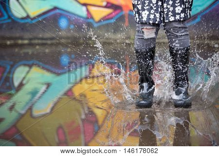 Girl jumping in the puddle in the street. Woman in grey rubber boots splashing in a puddle after rain. Pair of grey rubber boots jumping into a big puddle with grafiti refclections