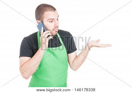 Market Employee Making Not Knowing Gesture At Phone