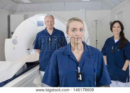 Female Medical Professional With Colleagues Standing By MRI Mach