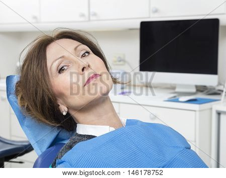Female Patient Sitting At Dentist's Clinic