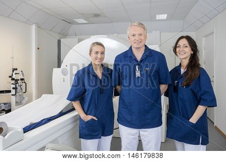 Confident Medical Colleagues Smiling By MRI Machine