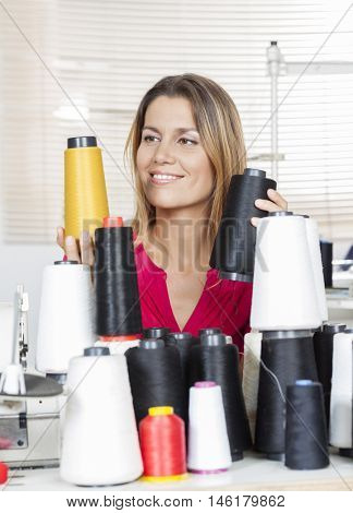 Happy Tailor Selecting Thread Spools At Workbench