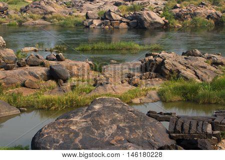 Hampi Tungabhadra river meadow. Landscape with water, palm, rock, stones India Karnataka