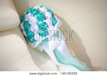 Wedding bouquet of fabric in color white and Tiffany. With rhinestones on a light background