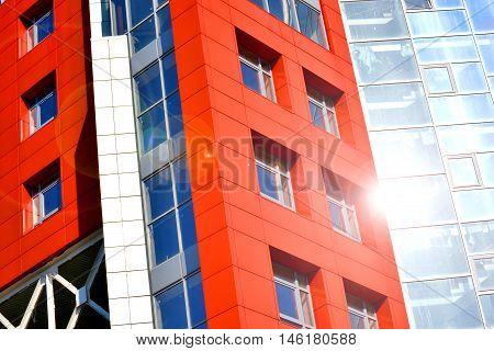 Part of the facade of modern building with red walls square windows the blue mirrored glass. Architecture in modern style and high-tech on bright sunny day. The building is photographed at an angle and sunny flare
