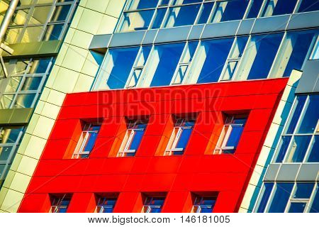 Part of the facade of a modern building with red walls square windows the blue mirrored glass. Architecture in a modern style and high-tech on a bright sunny day. The building is photographed at an angle