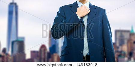 Businessman adjusting his necktie in front of a big city
