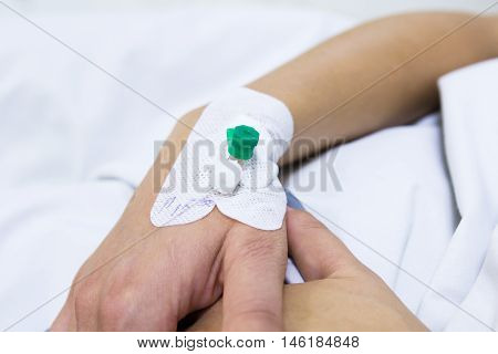 Injection cathetter in the hand of patient lying in the bed