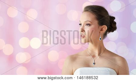 beauty, jewelry, wedding accessories, people and luxury concept - beautiful asian woman or bride with earring and pendant over rose quartz and serenity lights background