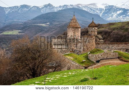 Aerial view of 9th-century Armenian Apostolic monastery located near the Tatev village in Armenia. Tree and mountains at the background. Cloudy sky in spring