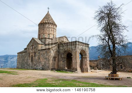 9th-century Armenian Apostolic monastery located near the Tatev village in Armenia. Tree and mountains at the background. Cloudy sky in spring