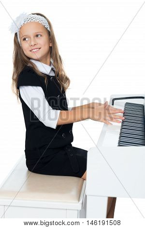 Beautiful little girl in the music school, learning to play the piano . the girl looked away from the piano - Isolated on white background