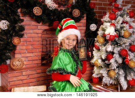 Little girl in suit of the Christmas Elf with old lamp near Xmas fir-tree and fireplace