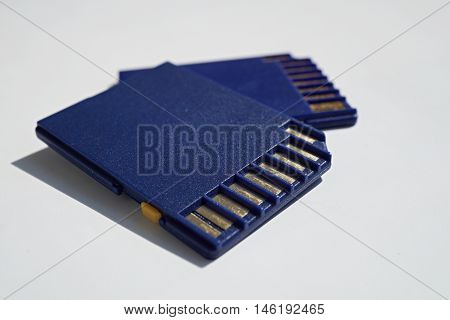 Two memory cards (SD card - Secure Digital card) used in video cameras and  computers in blue color with golden connectors as a symbol of technology used for home and professional entertainment