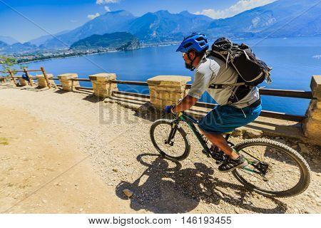 Mountain biking in sunny day man over Lake Garda on path Sentiero della Ponale, Riva del Garda, Italy