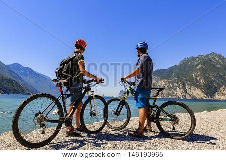 Mountain biking. Couple with bikes on Lake Garda, Riva del Garda, Italy.