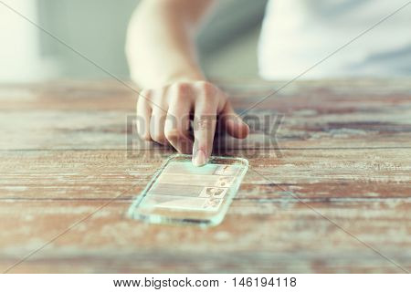 technology, news, mass media and people concept - close up of woman hand holding transparent smartphone with web page on screen at home