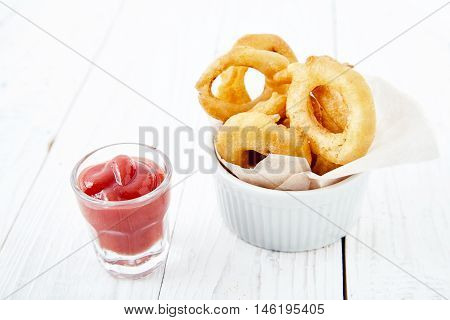 Close up shot of delicious, crunchy, golden onion rings in a white bowl with a paper, a ketchup shot next to it on wooden table. Appetizing flavorful snack for beer. Fastfood from the deep fryer.