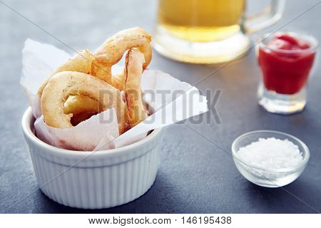 Close up shot of delicious, crunchy, golden onion rings in a white bowl with a paper, a cup of salt next to it. Appetizing tasty flavorful snack for beer. Fastfood from the deep fryer. Selective focus
