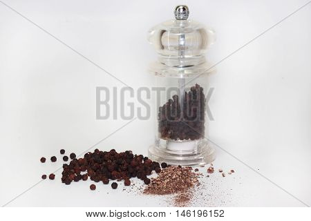 Black peppercorn background with mill isolated on white background