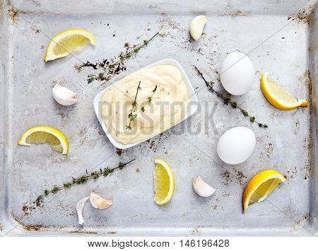 Delicious homemade hollandaise sauce or mayonnaise from next ingredients: butter, lemon juice, water, salt, eggs with adding garlic and thyme. Top view of gravy boat with sauce ingredients on metal