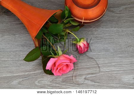 Capsize flower vase with roses. Water leaked out of a vase.