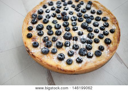 Close up of beautiful homemade blueberry pie on wooden background. Fresh pastry berries and sugar powder. Yummy home baked dessert food