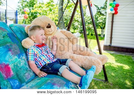 happy little boy sitting in a garden swing with a big teddy bear toy in the autumn, summer.